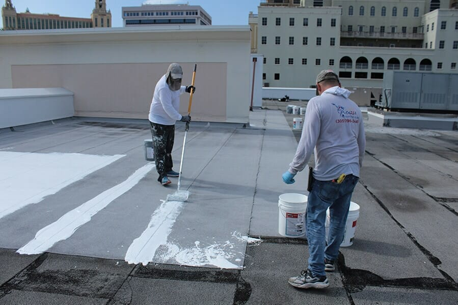 Workers on a roof applying silicone waterproofing coatings
